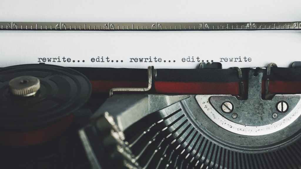"""A close-up of an old-fashioned typewriter displays the words """"rewrite...edit...rewrite...edit...rewrite"""""""